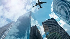 Airplane in the sky with modern buildings, with a blue sky - architectural acoustics external blocking noise from the exterior of the building - loud construction work outside the office