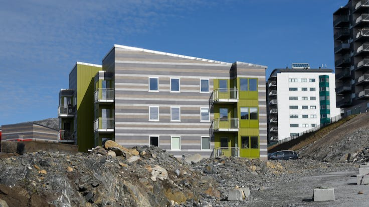 Multi-unit residential in Qinngorput, Nuuk, Greenland cladded with Rockpanel Woods Rhinestone Oak, Carbon Oak, Marble Oak and Rockpanel Colours RAL 095 50 50 in 8 mm Durable.