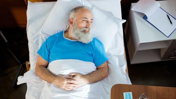 Illustrative image, healthcare, hospital, patient, elderly, man, bed, beard, pills, flip board