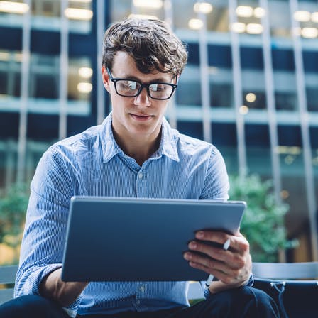 Young man using a tablet. Photo used in Sustainability Report 2019.  People, person, man, young man