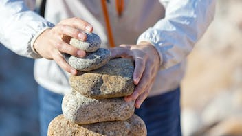 Young person stacking stones at the beach
