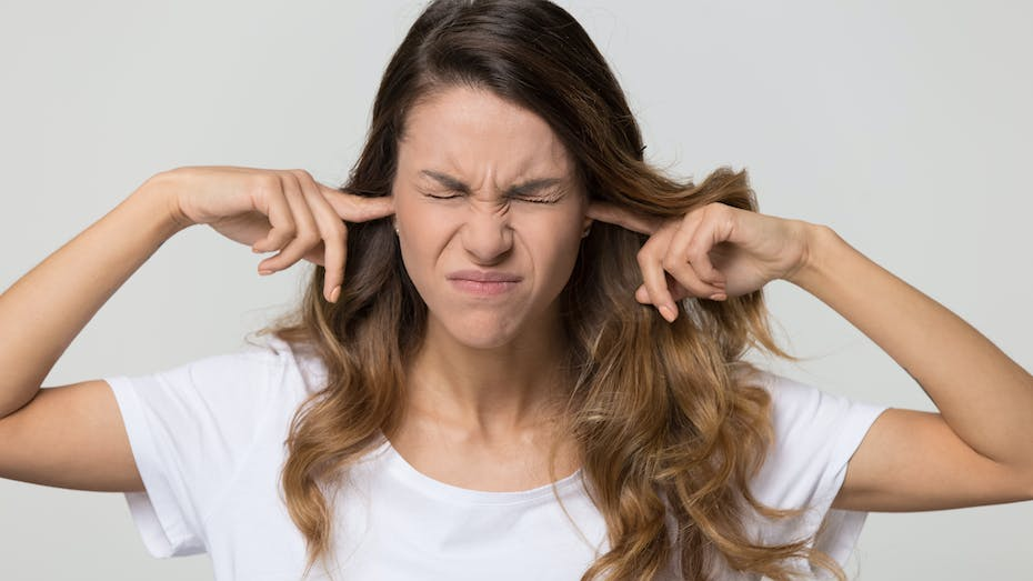 Woman putting her fingers in her ears