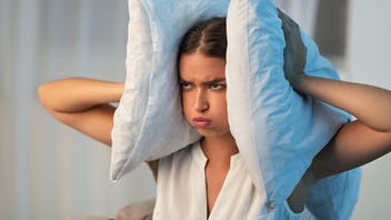 Annoyed Young Lady Covering Ears With Pillow Irritated Because Of Noise At Home.