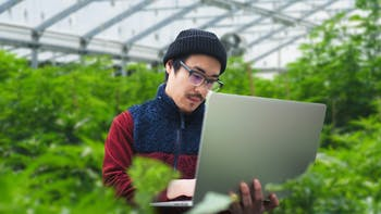 e-Gro grower in greenhouse with laptop in sweater and hat for grodan101