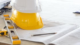 Safety helmet for engineer and architect on working desk/table with drawing/blueprint and tools at job site, engineer/architect for construction work concept - building codes and standards for construction.