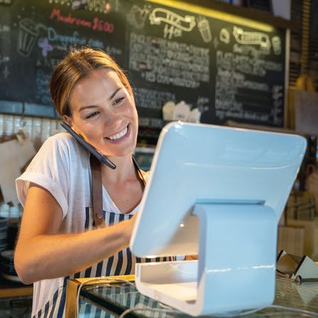 Waitress talking on the phone at a restaurant - vendor / supplier relationship