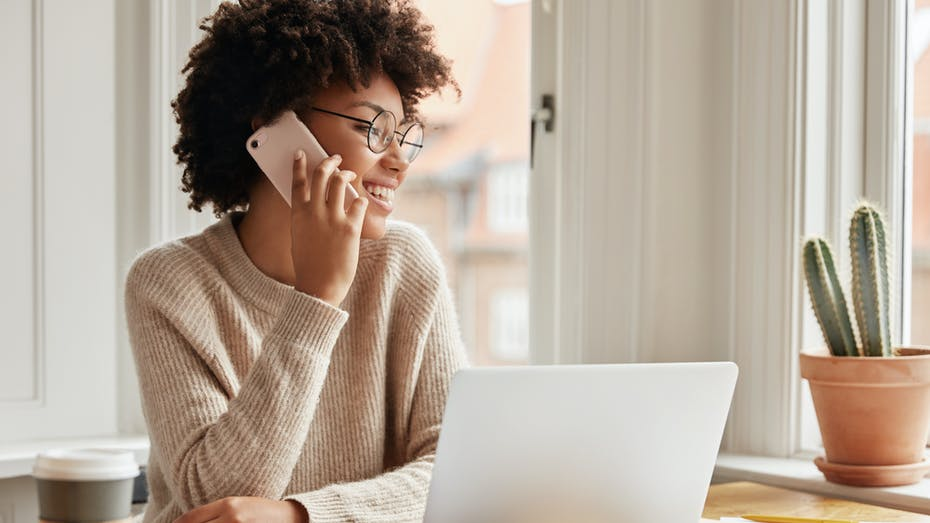 Happy, smiling young woman working from home on a laptop, holding a mobile phone.