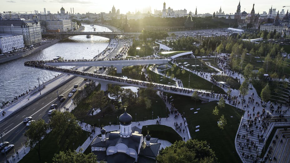 Moscow, Park Zariadye, soaring bridge, city, nature, people, architecture. September 2017.  Green grass, trees and a church in the city centre. Sunset view on the Kremlin