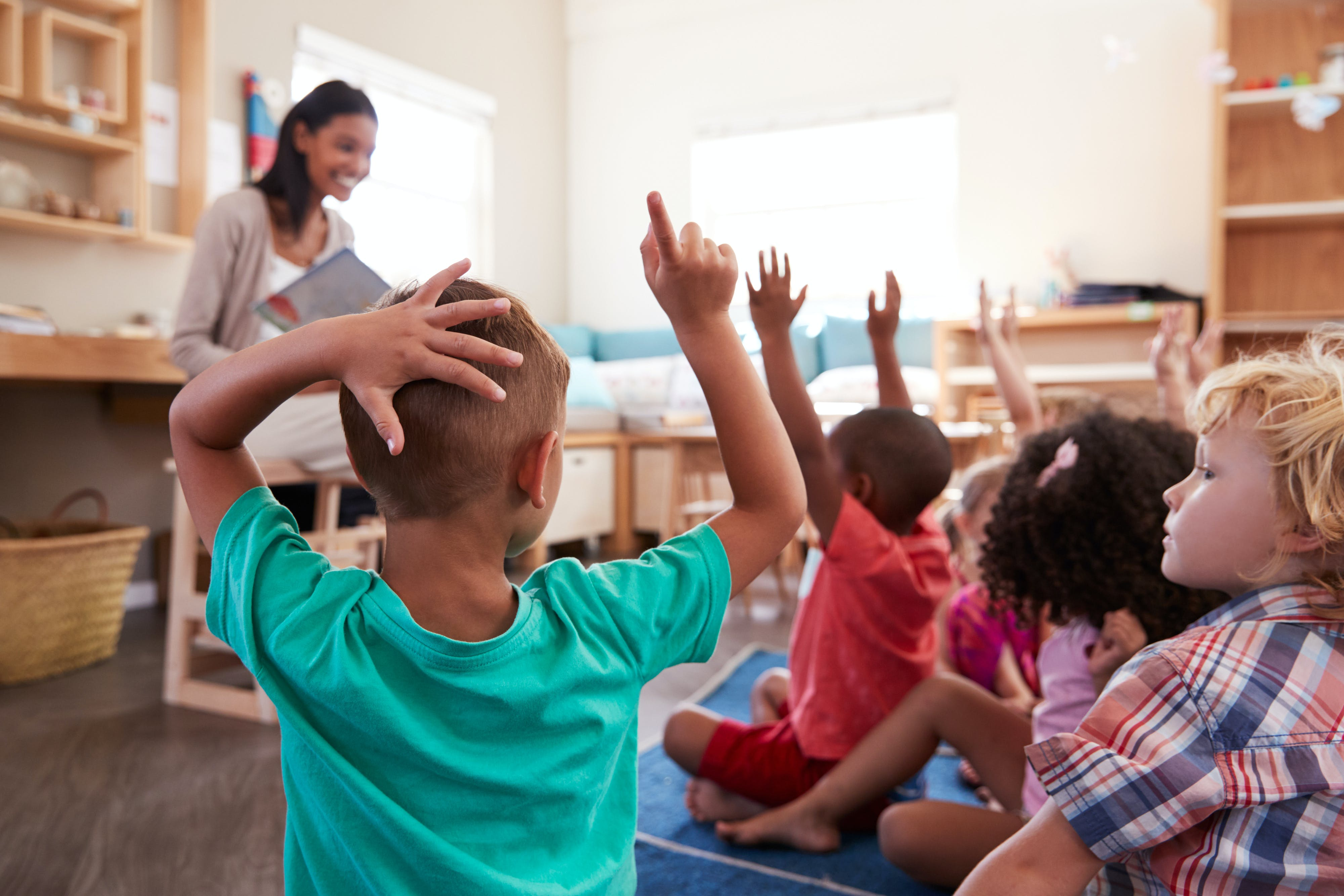 Pupils At A School Raising Hands To Answer Question
