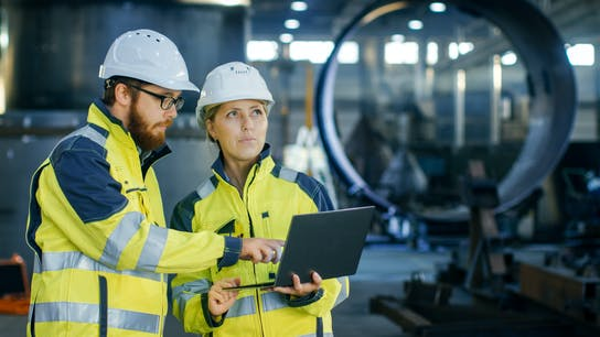 Male and Female Industrial Engineers in Hard Hats Discuss New Project while Using Laptop. They Make Showing Gestures. They Work in a Heavy Industry Manufacturing Factory.