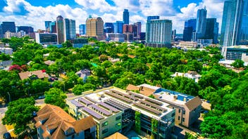 Sustainable urban development practices with homes and buildings integrated into the natural environment. The future of Austin Texas a renewable energy sustainable city.