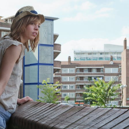 Woman on rooftop looking at the surroundings. Balcony. High-rise. Apartments. Flats.