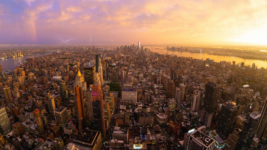 New York City skyline with Manhattan skyscrapers at dramatic stormy sunset, USA.